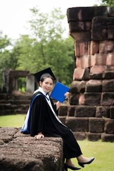Graduados da fêmea do retrato vestem a graduação azul.