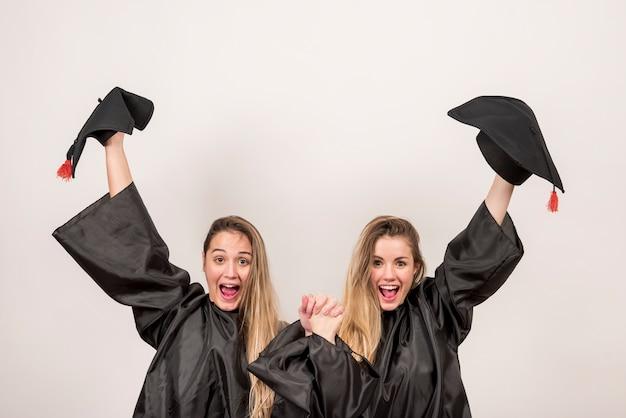 Graduados entusiastas segurando trenchers