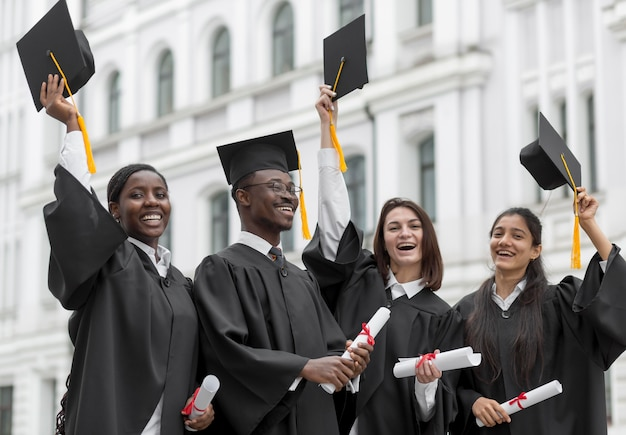 Graduados felizes jogando bonés para cima