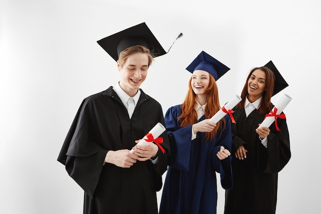 Graduados internacionais felizes que sorriem regozijando-se guardando diplomas.