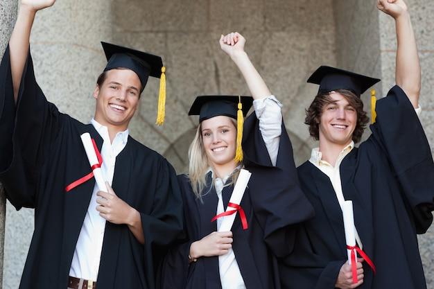 Graduados que detêm seu diploma ao levantar o braço