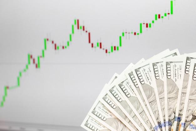 Gráfico de crescimento de moeda forex e notas de cem dólares