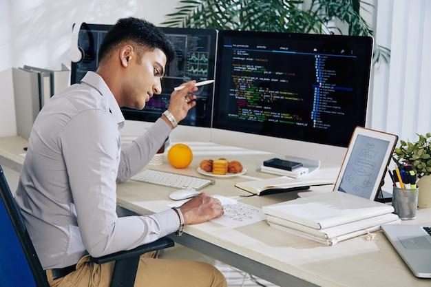 Gráfico de estrutura de verificação de desenvolvedor indiano pensativo ao trabalhar em código de programação em seu escritório