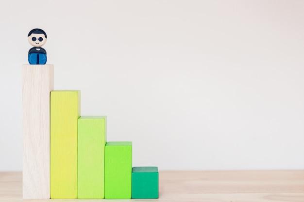 Gráfico de informação de blocos de brinquedo gráfico stair bar com brinquedo de homem de negócios, sente-se no bloco mais alto,