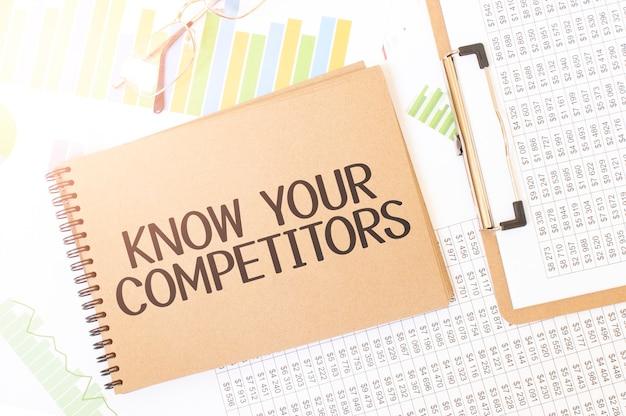 Gráfico de negócios em uma folha de bloco de notas de artesanato colorido com a placa conheça seus concorrentes. bloco de notas na mesa com documentação financeira