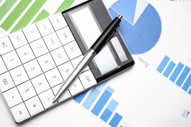 Gráfico de negócios mostrando sucesso financeiro no mercado de ações com caneta e calculadora