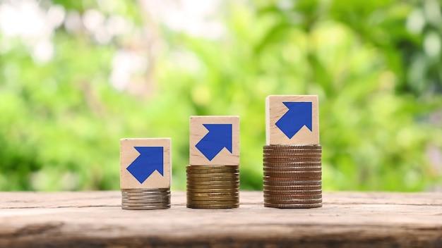 Gráfico de seta em blocos de madeira em uma pilha de ideias de crescimento de negócios de moedas ou ideias de etapa de sucesso financeiro. lucro no investimento