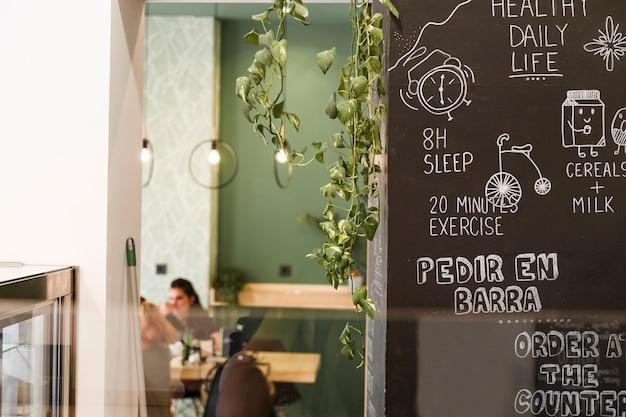 Gráfico de vida diária saudável na parede preta no café