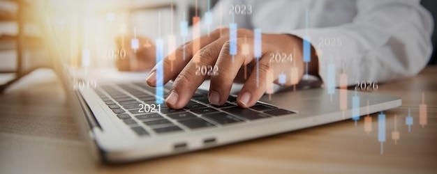 Gráfico do mercado de ações empresarial com a mão do homem de negócios e do investidor financeiro digitando no laptop