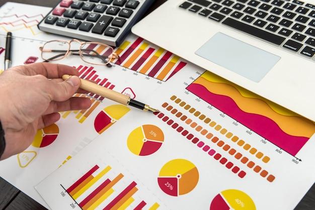 Gráfico financeiro com caneta para laptop e calculadora para analista financeiro, trabalho no escritório