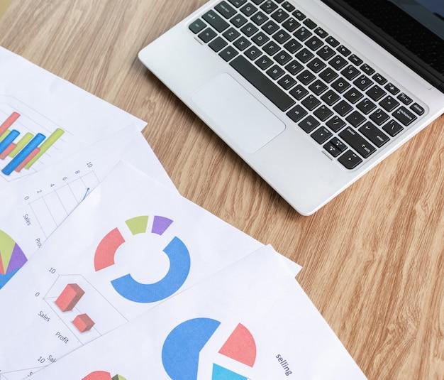 Gráfico na análise de mesa e laptop com negócios