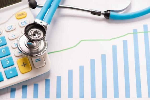 Gráficos de análise financeira de prática médica com estetoscópio e calculadora. fechar-se