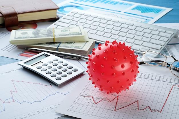 Gráficos e histogramas, notas de dólar e coronavírus na mesa
