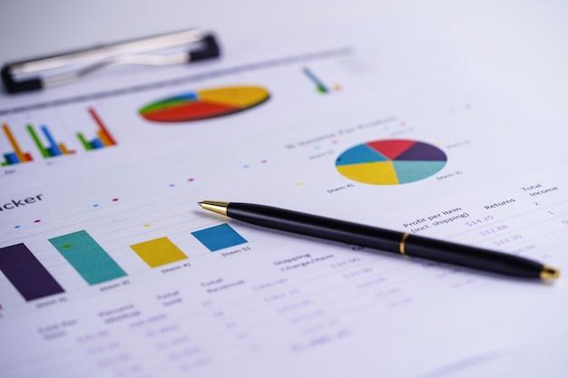 Gráficos e relatório de papel gráfico com caneta.