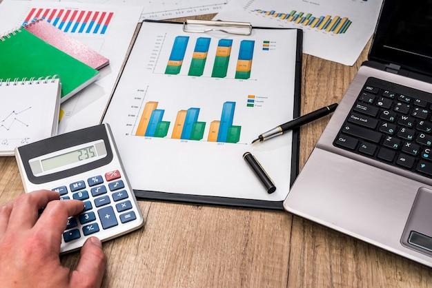 Gráficos financeiros com laptop, calculadora, caneta na mesa.