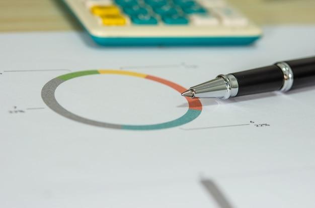 Gráficos financeiros de negócios e caneta.