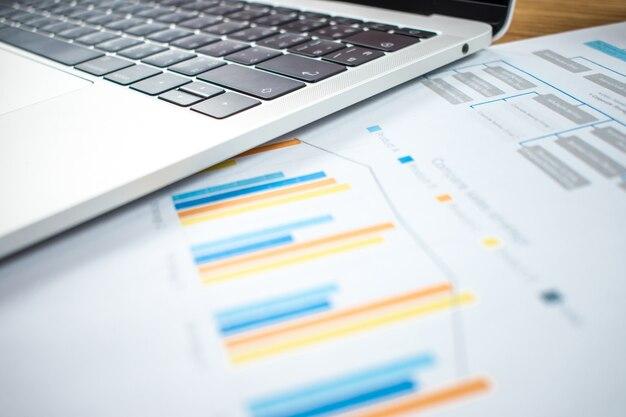 Gráficos financeiros e computadores estão na mesa de madeira no conceito de negócio.