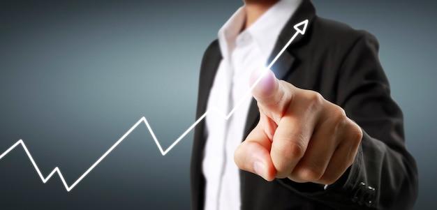 Gráficos tocantes de mão de indicador financeiro e gráfico de análise de economia de mercado contábil