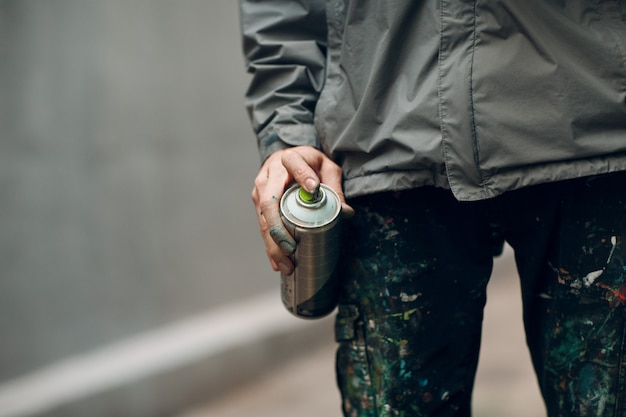 Grafiteiro em roupas manchadas com spray de tinta pode na mão
