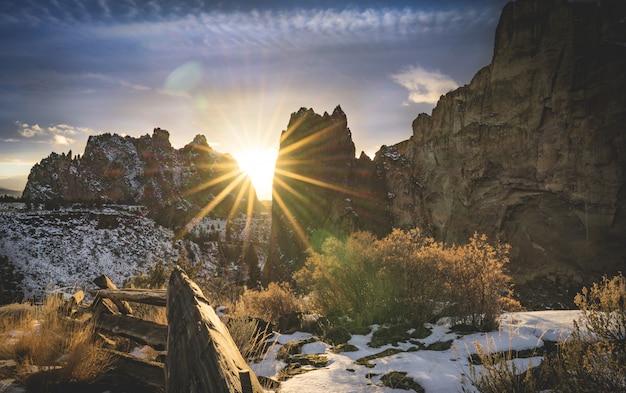 Grama coberta de neve perto de desfiladeiros durante o pôr do sol