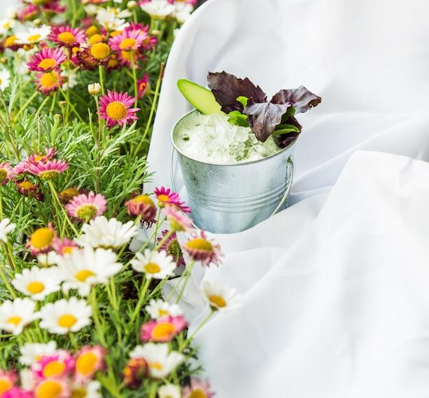 Grama com flores, toalha de mesa de piquenique e um copo de iogurte com ervas.