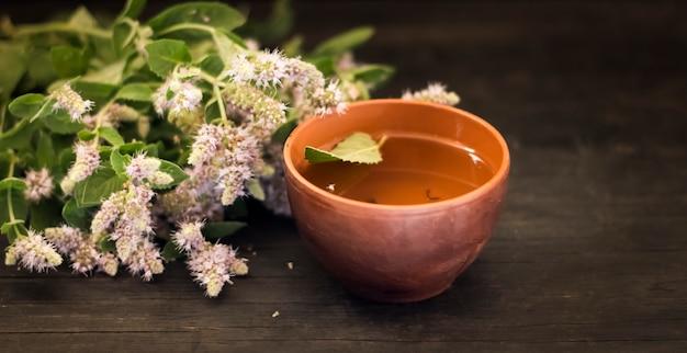 Grama de hortelã florescendo com uma xícara de chá em uma mesa escura.