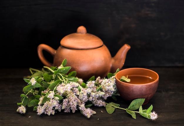 Grama de menta florescendo com uma xícara de chá de barro e um bule de chá em uma mesa de madeira escura
