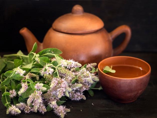 Grama de menta florescendo com uma xícara de chá e um bule de chá em uma mesa de madeira escura