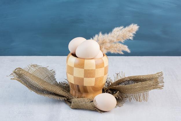 Grama de penas caules e ovos em uma tigela quadriculada na mesa de mármore.