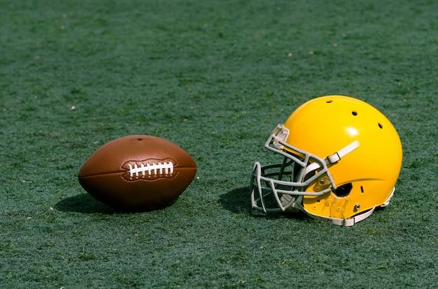 Grama do estádio com capacete e bola de futebol nele. adequado para o fundo.