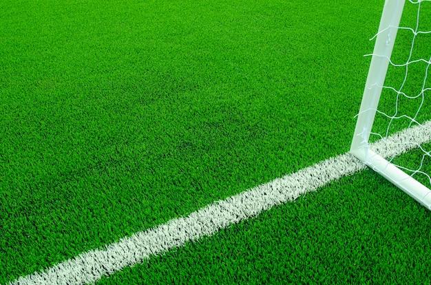 Grama verde artificial com listras brancas no campo de futebol