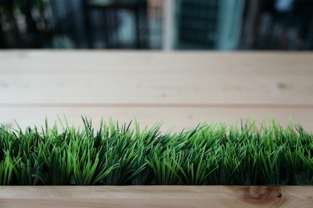 Grama verde artificial disposta na linha horizontal na frente da mesa de madeira de prancha desfocar o fundo.