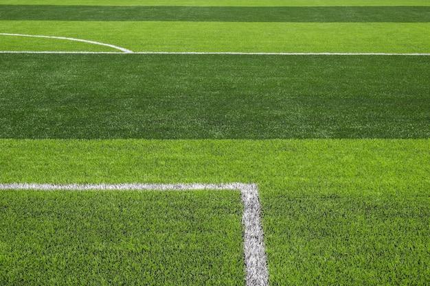 Grama verde brilhante e escura artificial no futebol ao ar livre ou estádio de futsal