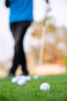 Grama verde com close-up de bola de golfe em foco suave ao sol