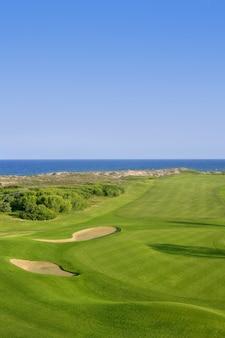 Grama verde do campo de golfe perto do oceano do mar