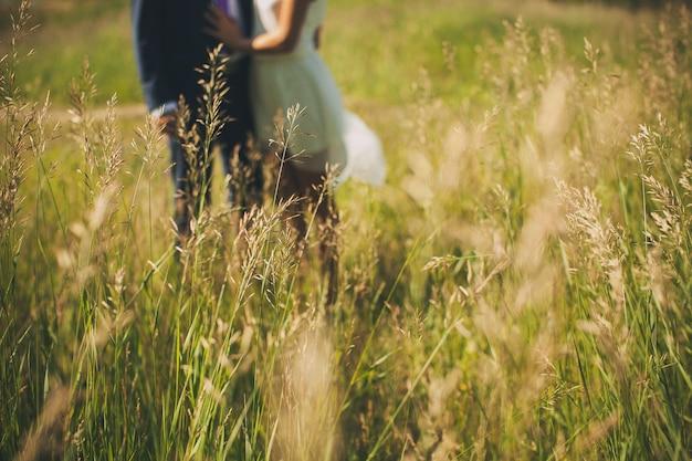 Grama verde no campo em um dia de verão ensolarado, no indivíduo e na menina borrados, recém-casados.