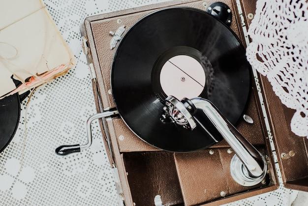 Gramofone com um disco de vinil na toalha de mesa de malha