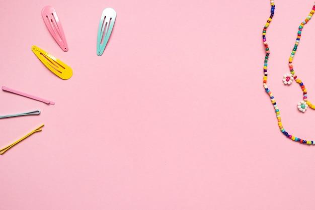 Grampo de acessórios em tons pastel coloridos em fundo rosa close-up moderno moderno do passado