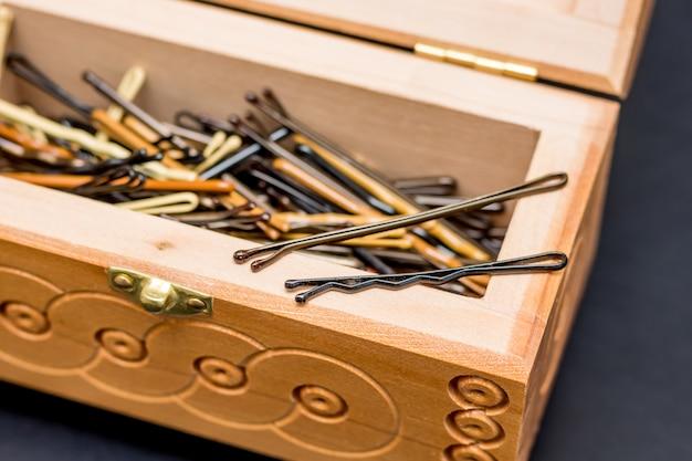 Grampos de cabelo em um caixão em cima da mesa no salão de cabeleireiro para criar um penteado elegante