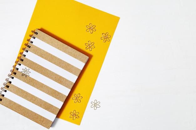 Grampos melal do withgold liso da configuração, copybook da forma para escrever e desenhar no espaço de trabalho do tabletop com espaço da cópia. vista do topo.