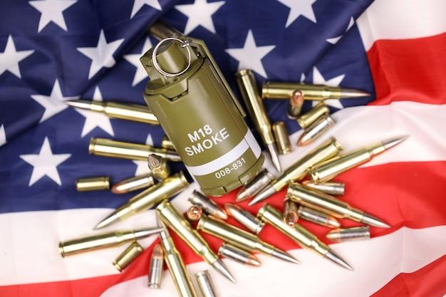 Granada de fumaça m18 e muitas balas e cartuchos amarelos na bandeira dos estados unidos. conceito de tráfico de armas em território dos eua ou operações especiais