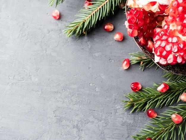 Granada vermelha suculenta descascada em um prato vintage na árvore de natal