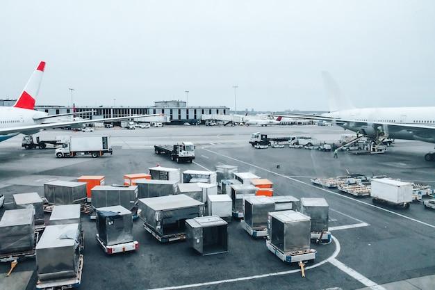 Grande aeroporto com carros, contêineres e aviões