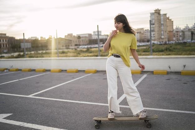Grande angular de uma garota em um skate em um parque