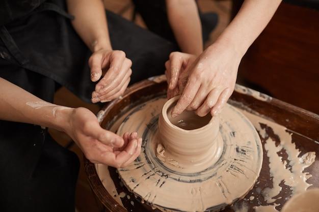 Grande ângulo, close-up de duas pessoas moldando argila na roda de oleiro, conceito de arte e artesanato, espaço de cópia