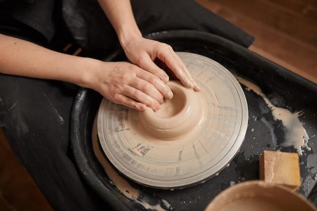 Grande ângulo, close-up de elegantes mãos femininas modelando argila na roda de oleiro na oficina, copie o espaço