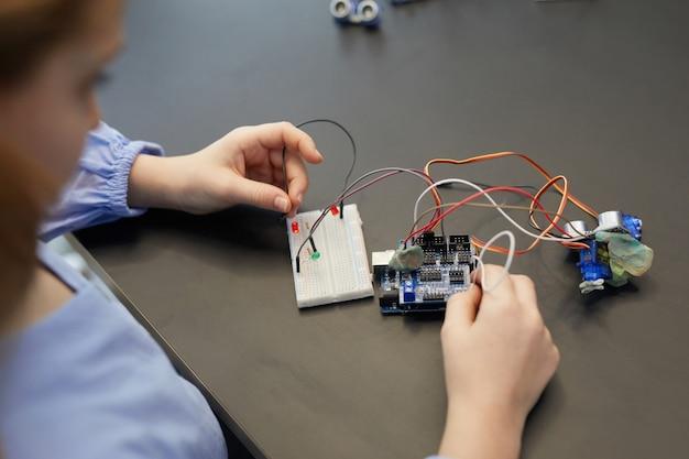 Grande ângulo, close-up de uma criança experimentando circuitos elétricos enquanto construía robôs durante a aula de engenharia na escola de desenvolvimento