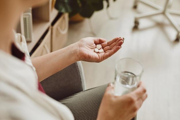 Grande ângulo close-up de uma mulher irreconhecível segurando comprimidos e um copo de água, medicamento e tratamento de recuperação, espaço de cópia
