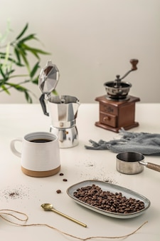 Grande ângulo da xícara de café com moedor na mesa