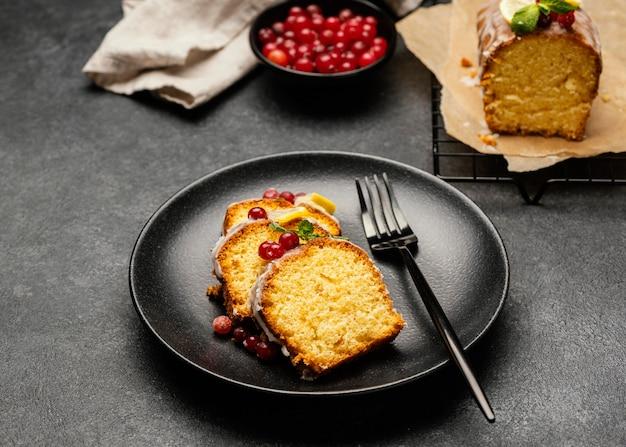 Grande ângulo das fatias de bolo no prato com garfo e frutas